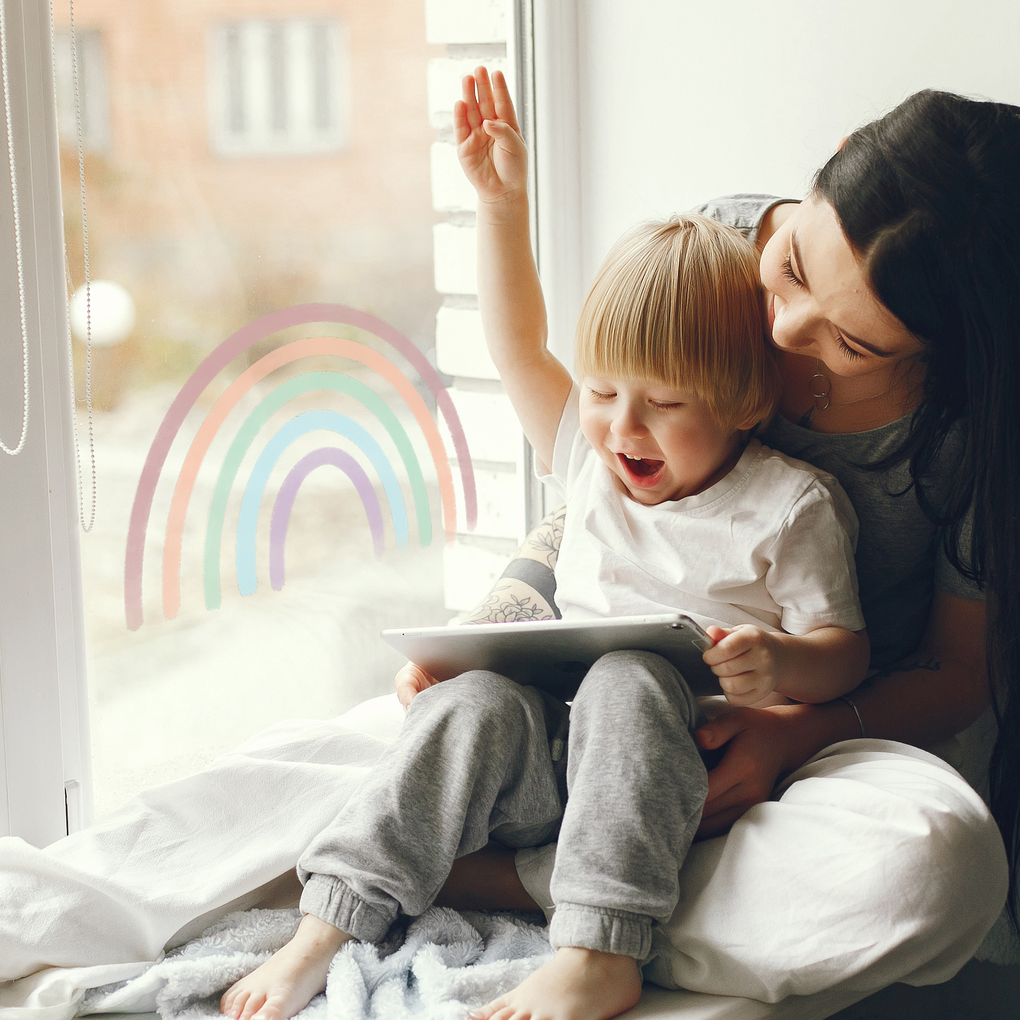 Beautiful woman with child. Woman in a gray t-shirt. Family sitting on a windowsill.